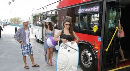 photo of people in front of an rta bus with beach gear