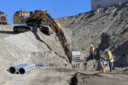 Excavator and crew digging drainage